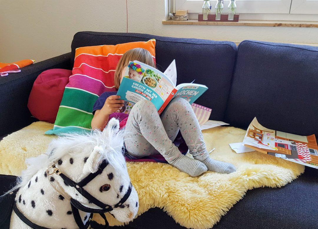 Die Dreijährige sucht sich Projekte im Corona Beschäftigungsbuch aus.